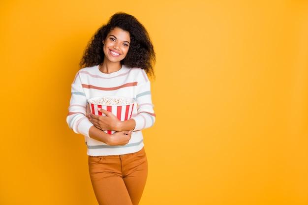 Портрет радостной милой девушки, держащей в руках попкорн, изолировал стену желтого цвета