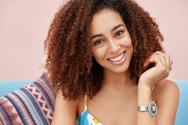 넓은 유쾌한 미소를 지닌 기쁜 어두운 피부의 여성의 초상화는 곱슬 머리를 가지고 있으며 집이나 식당에서 좋은 휴식을 취하며 긍정적 인 소식을 듣고 기쁩니다.