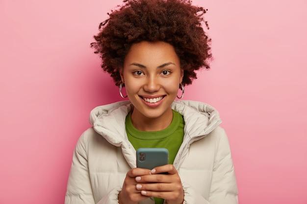 嬉しい暗い肌のヒップスターの女の子の肖像画は、携帯電話を使用し、電子メールボックスをチェックし、暖かい冬のコートを着て、ピンクの壁に隔離され、ウェブサイトをネットワーク化する