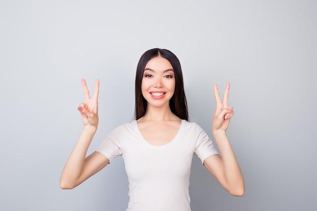 Портрет счастливой девушки, показывающей два символа мира