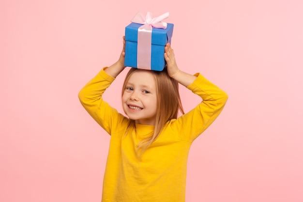 머리에 선물 상자를 들고 현재를 즐기고 카메라, 생일 또는 크리스마스 축하에 즐겁게 웃는 행복한 어린 소녀의 초상화. 분홍색 배경에 고립 된 실내 스튜디오 촬영