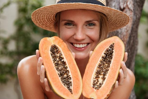 Портрет радостной прекрасной женщины позирует обнаженной, в летней шляпе, держит в руках органическую экзотическую папайю