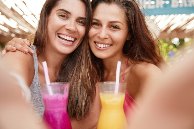쾌활한 표정으로 기쁜 젊은 여성의 초상화, 칵테일을 들고 셀카 만들기, 하얀 완벽한 치아를 보여주고 넓은 미소를지었습니다.