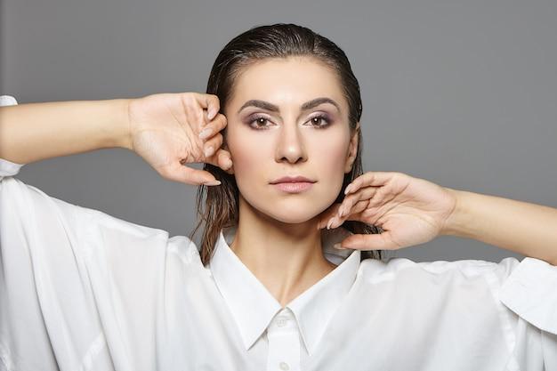 검은 젖은 머리카락을 뒤로 빗질하고 연기가 자욱한 눈을 가진 매력적인 남녀 양성 젊은 여성의 초상화는 특대 흰색 실크 셔츠를 입고 실내에서 포즈를 취합니다.