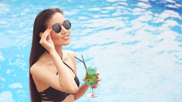Портрет гламурной брюнетки в солнечных очках с коктейлем в руках