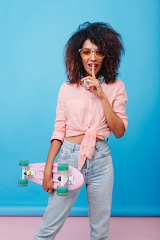 指で唇に触れる薄茶色の肌を持つ魅力的な巻き毛の女の子の肖像画。青い部屋でポーズをとってスケートボードを持つアフリカの女性の屋内写真。