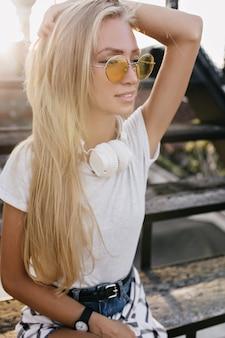 彼女の長いブロンドの髪に触れている魅力的な日焼けした女性の肖像画。