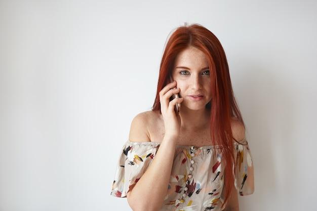 ピザの配達を注文し、電話で会話している長い生姜髪とそばかすを持つ魅力的なトレンディな見た目のかわいい女の子の肖像画。人、現代のライフスタイル、テクノロジー、コミュニケーションのコンセプト
