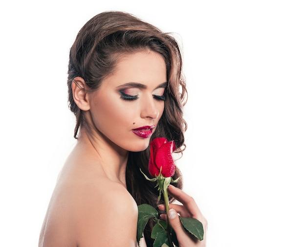 빨간 장미와 함께 매력적인 여자의 초상화입니다. 흰색 절연