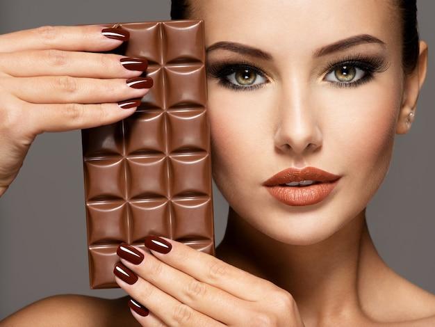 Портрет гламура красивая женщина с коричневыми ногтями держит плитку шоколада