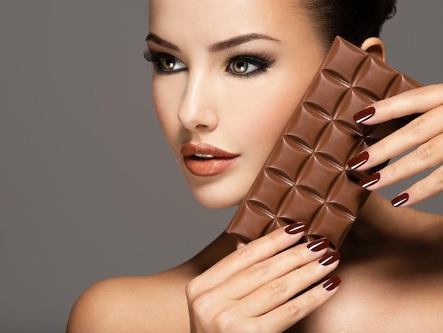 갈색 손톱으로 매력적인 아름 다운 여자의 초상화 보유 초콜릿 바