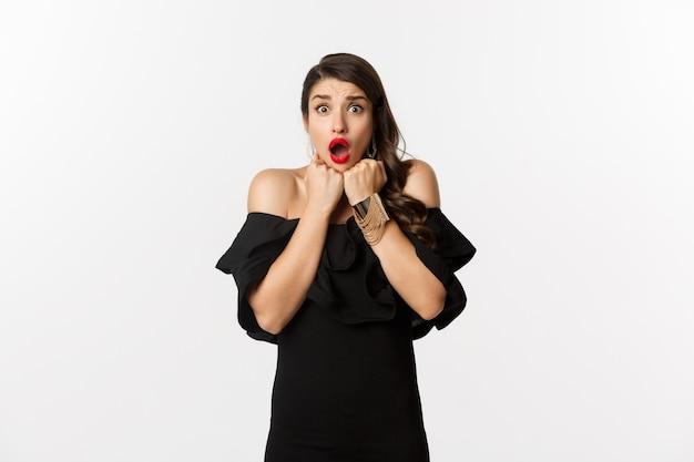 Портрет гламурной женщины, испуганной и шокированной в камеру, смотрящей на что-то со страхом, стоящей в черном платье на белом фоне.