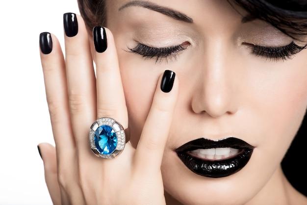 매력적인 여자의 손톱, 입술 및 눈의 초상화는 검은 색으로 칠해졌습니다.