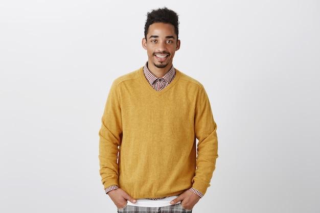 주머니에 손을 잡고 세련된 노란색 풀오버에 아프로 헤어 스타일을 가진 잘 생긴 아프리카 계 미국인의 초상화, 부담없이 웃고