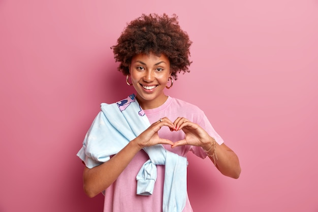 見栄えの良いアフリカ系アメリカ人女性のポートレートは、ハートサインを示し、笑顔でロマンチックな感情を幅広く表現し、愛の告白をする誰かを気遣う、肩にジャンパーを結んだカジュアルなtシャツを着る