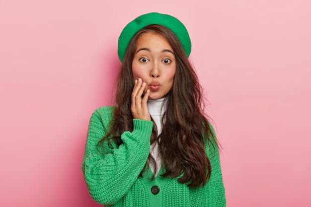 검은 머리를 가진 잘 생긴 아시아 여성의 초상화, 입술을 둥글게 유지하고 남자 친구에게 키스하고 녹색 베레모와 스웨터를 입고