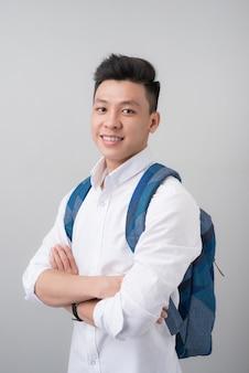 Портрет симпатичного азиатского студента на сером фоне.
