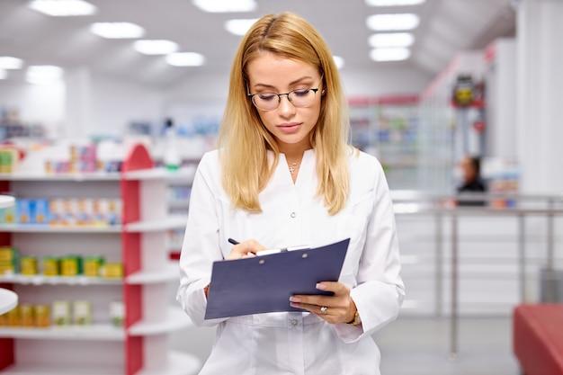 Портрет красивой блондинки приятной женщины-фармацевта, пишущей в буфере обмена