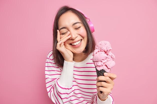 格好良いブルネットのアジアの女性の肖像画は顔に手を保ちます目を閉じた笑顔は広く暇な時間を楽しんでいますピンクの壁に隔離された縞模様のジャンパーに身を包んだおいしい食欲をそそるアイスクリームを保持します