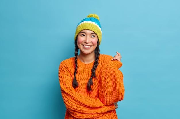 두 개의 땋은 머리와 좋은 찾고 갈색 머리 아시아 여자의 초상화는 파란색 벽 위에 절연 겨울 옷을 입고 즐거운 무언가에 대한 낭만적 인 표현 꿈을 가지고