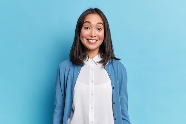 格好良いブルネットの女性の肖像画は歯を見せて歯を見せて、屋内でカジュアルなジャンパーとシャツのモデルを着て楽しいものを聞きます