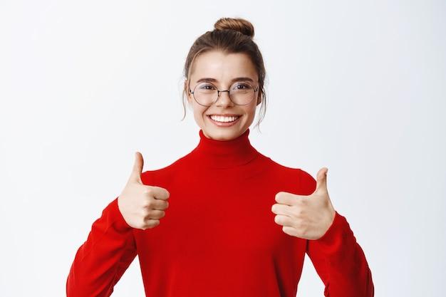 Портрет красивой бизнес-леди в очках хвалят отличную работу, показывая большие пальцы, чтобы одобрить и что-то лайкать, давая положительный отзыв и улыбаясь, белая стена