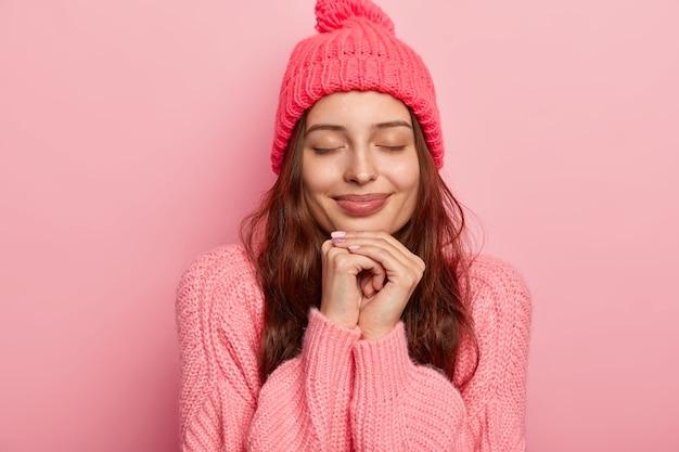 잘 생긴 매력적인 여자의 초상화는 턱 아래에 양손을 유지하고, 눈을 감고, 생각에 깊이 빠져 있고, 장미 빛 스튜디오 벽 위에 모델, 스웨터와 모자를 입고
