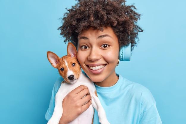 格好良い陽気なアフロアメリカ人女性の肖像画は、顔の笑顔の近くに小さな子犬を保持し、青い壁に隔離されたステレオヘッドフォンを身に着けているお気に入りの犬と一緒に楽しい時間を楽しんでいます。
