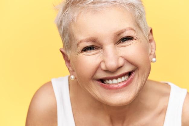 Портрет симпатичной жизнерадостной европейской женщины средних лет со стильной прической в белой майке, выражающей положительные эмоции, широко улыбающейся, с прямыми зубами, радостной получать хорошие новости