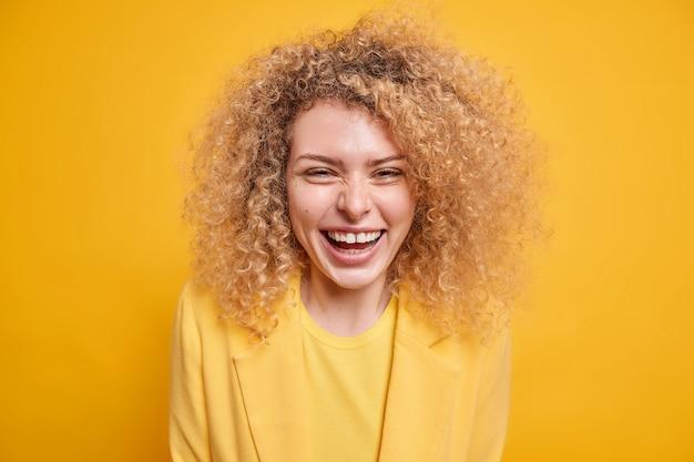 잘 생긴 곱슬머리 젊은 여성의 미소는 최근 소식을 듣고 기쁘게 긍정적인 감정을 광범위하게 표현합니다.