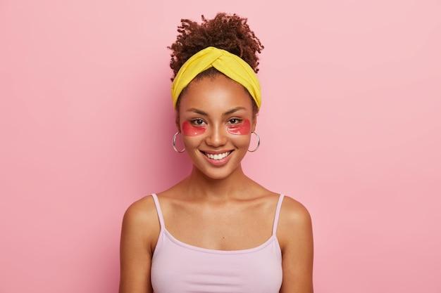 見栄えの良い暗い肌の若いアフリカ系アメリカ人女性の肖像画は、化粧品のコラーゲンパッチを着用し、ヘッドバンドとカジュアルなtシャツを着用しています