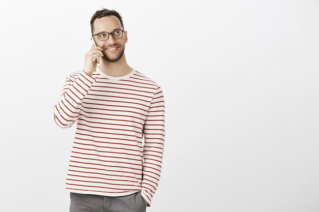 トレンディなメガネとカジュアルな衣装を着た見栄えの良いフレンドリーな男性の肖像画。スマートフォンで友達に電話しながら見上げる