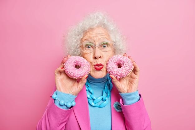 見栄えの良い白髪の女性のポートレートは、顔の近くにドーナツを持ち、唇を丸くし、人生を楽しんでいる、甘い歯は眼鏡をかけているファッショナブルな服を着ている