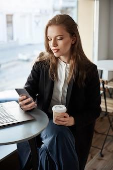ラップトップで仕事の休憩をとって、カフェの近く、窓の近くに座って、コーヒーを飲みながら、スマートフォンで閲覧して、見栄えの良いモダンな女性の肖像画
