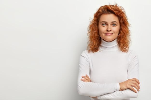 잘 생긴 빨간 머리 여자의 초상화는 작은 미소로 보이고, 차분한 얼굴 표정을 가지고 있으며, 팔을 접은 채로 유지하고, 흰색 터틀넥을 착용하고, 혼자 포즈를 취하고, 흰 벽에 고립 된 즐거운 의견을 듣고 있습니다.