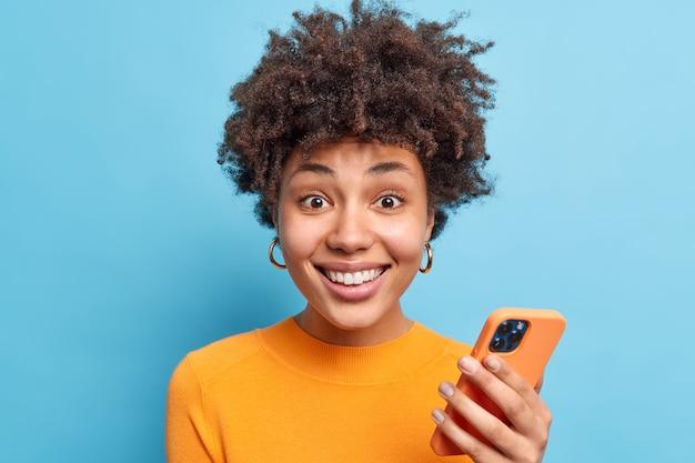 巻き毛の格好良い笑顔の若い女性の肖像画は、オンラインダウンロードのチャットに携帯電話を使用しています新しいアプリは、青い壁に隔離されたオレンジ色のジャンパーを喜んで着ています