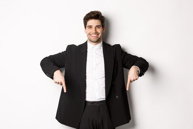 검은 양복을 입은 잘 생긴 세련된 남자의 초상화, 손가락을 아래로 가리키고 웃고, 겨울 방학 프로모션을 보여주고, 흰색 배경 위에 서 있습니다.