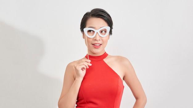 見栄えの良いスタイリッシュな若い女の子の肖像画は、スティックにメガネのフェイスマスクを持ってパーティーに出席し、笑顔で問題がない、立っている白い背景を見る