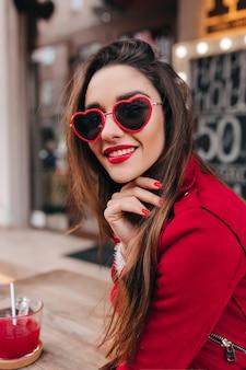 Портрет красивой белой девушки в солнечных очках в форме сердца, позирующей со счастливой улыбкой