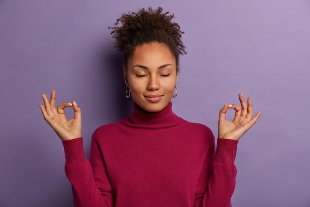 잘 생긴 여자의 초상화는 명상하고, 양손을 괜찮은 제스처로 유지하고, 눈을 감고, 퇴근 후 휴식을 취하기 위해 요가를 연습합니다.