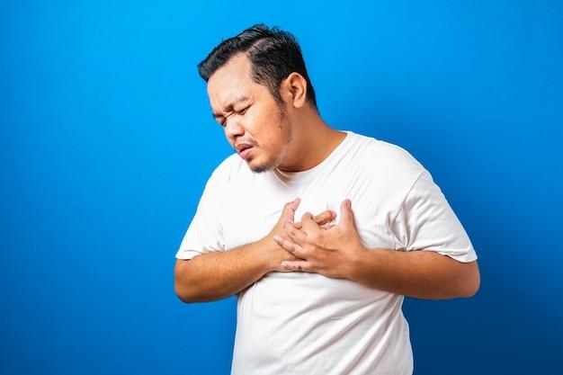 彼の胸に痛みを持っている白いtシャツの格好良い若いアジア人男性の肖像画