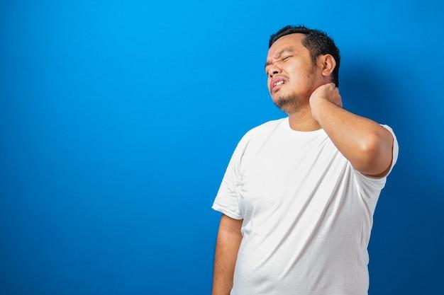 彼の首に痛みを持っている白いtシャツの格好良い若いアジア人男性の肖像画