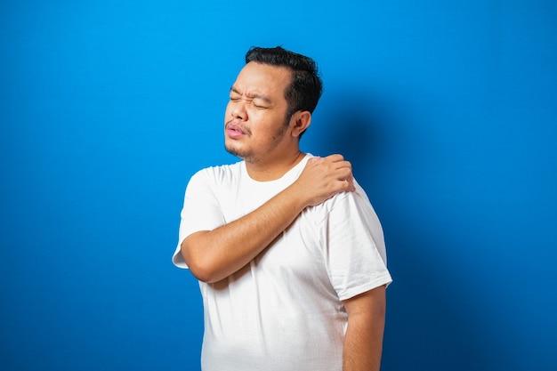 彼の肩に痛みを持っている白いtシャツの格好良い若いアジア人男性の肖像画
