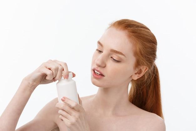 灰色の免疫システムと健康の世話をしようとすると、錠剤を保持している見栄えの良い若い白人女性の肖像画