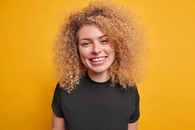 캐주얼 블랙 티셔츠 미소를 입은 곱슬 덥수룩 한 머리를 가진 잘 생긴 젊은 유럽 여성의 초상화는 기쁨으로 노란색 벽 웃음 위에 고립 된 긍정적 인 감정을 광범위하게 표현합니다.