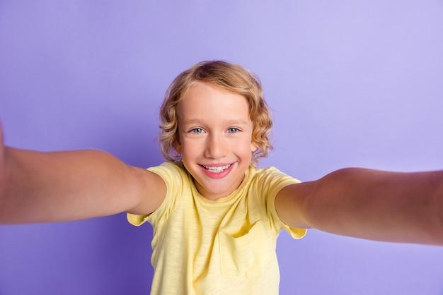 良い気分の子供の男の子の肖像画は、紫色の背景の上に分離されたカジュアルなスタイルの服を着て自分撮りの歯を見せる笑顔を作ります