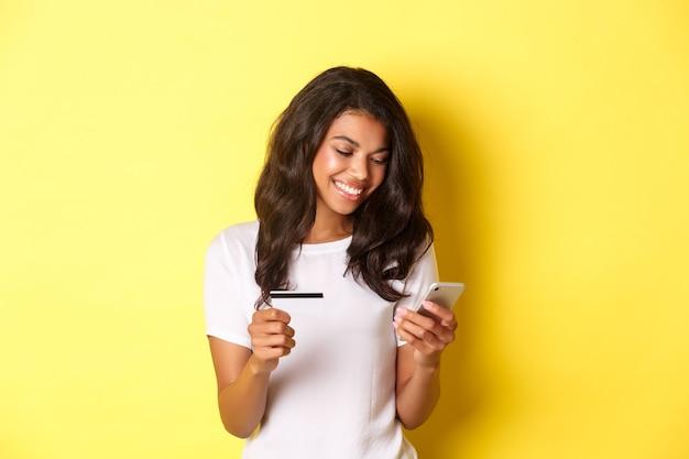 스마트폰과 신용카드 거치대로 온라인 쇼핑을 하는 잘 생긴 아프리카계 미국인 여성의 초상화...