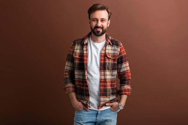 Портрет красивого привлекательного стильного бородатого мужчины на коричневом
