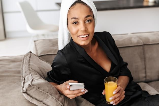 自宅で携帯電話とジュースを使用して、バスローブを着てゴージャスなアフリカ系アメリカ人女性の肖像画