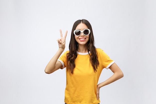 Портрет великолепной азиатской женщины, смотрящей в камеру с улыбкой и показывающей знак мира